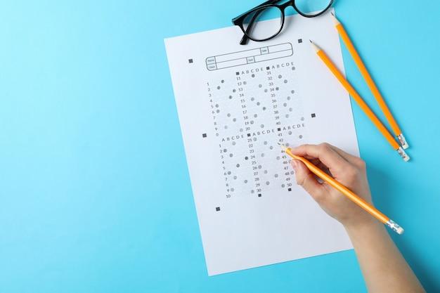 Student füllt antworttestblatt auf blauer oberfläche, draufsicht Premium Fotos