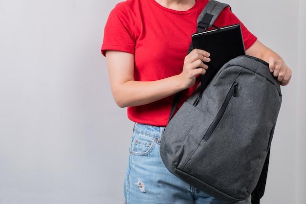 Student hält den grauen rucksack vorne
