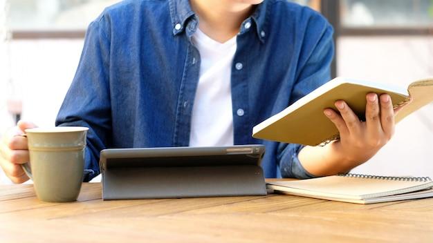 Student hält notizbuch und verwendet digitales tablet