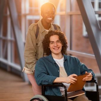 Student hilft einem kollegen im rollstuhl