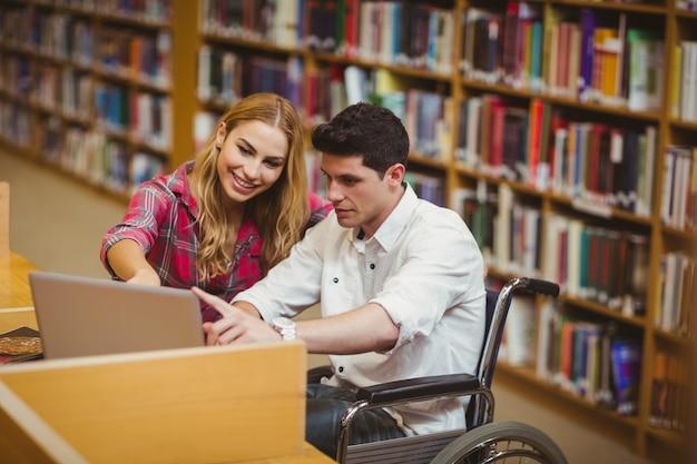 Student im rollstuhl, der mit einem mitschüler in der bibliothek arbeitet
