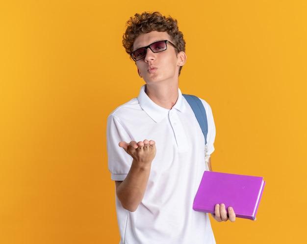 Student in freizeitkleidung mit brille mit rucksack, der ein buch hält und einen kuss bläst, der die hand vor ihm hält, die über orangefarbenem hintergrund steht