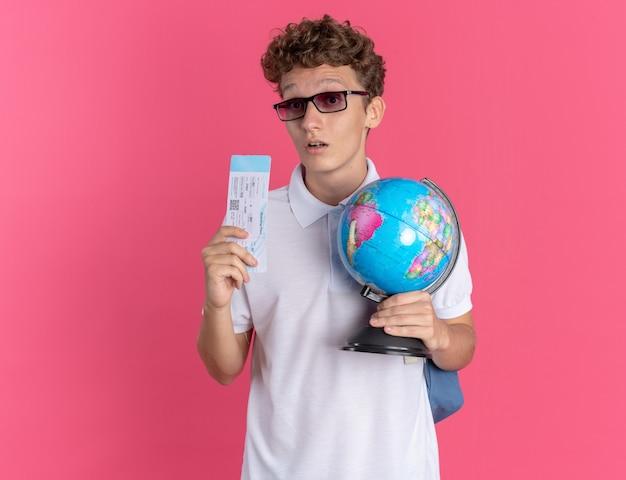Student in freizeitkleidung mit brille mit rucksack, der globus und flugticket hält und die kamera verwirrt auf rosafarbenem hintergrund betrachtet