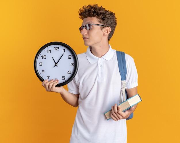Student in freizeitkleidung mit brille mit rucksack mit buch und globus, der mit ernstem gesicht auf orangefarbenem hintergrund beiseite schaut