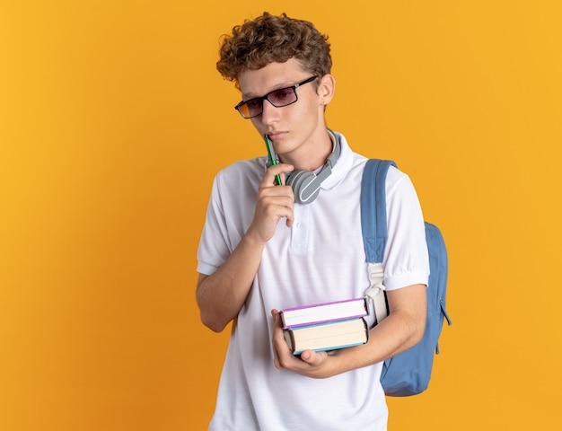 Student in freizeitkleidung mit kopfhörern mit brille und rucksack mit büchern, die verwirrt auf orangefarbenem hintergrund stehen