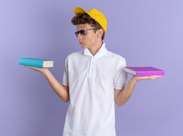 Student in weißem poloshirt und gelber mütze mit brille, die notizbücher hält