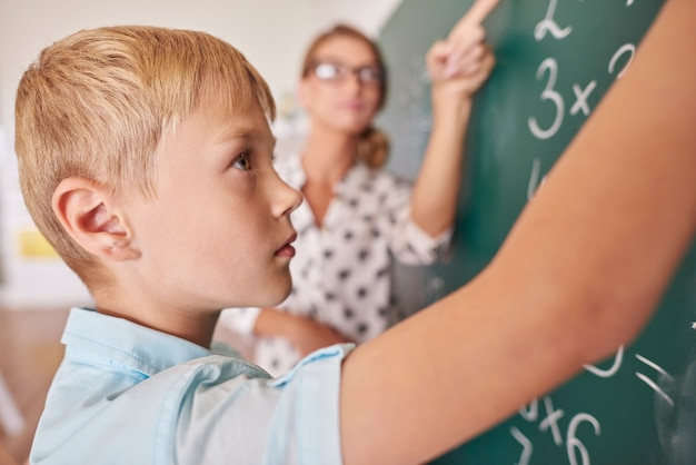 Student junge, der matheproblem an tafel tut