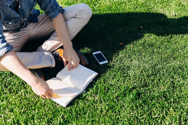 Student liest ein buch, das auf dem grünen rasen vor der modernen bibliothek sitzt