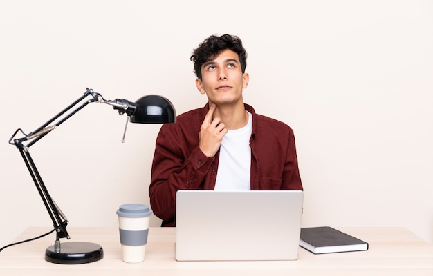 Student mann an einem arbeitsplatz mit einem laptop