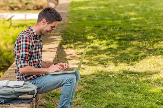 Student mit buch student, der hausarbeit im park tut.