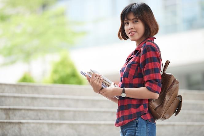 Student mit dem rucksack und lehrbüchern, die an kamera sich wenden