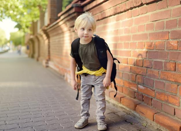 Student mit großem rucksack nahe dem schulgebäude.