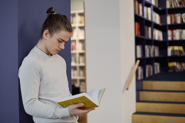 Student mit haarknoten, der in der bibliothek steht, isolierte leseinformationen in offenem lehrbuch auf seinen händen, während er forschung macht