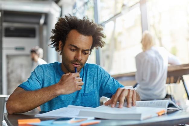 Student mit lockigem haar und borsten, die konzentriert schauen, während sie etwas wichtiges im buch lesen, das stift am kinn hält. fleißiger mann, der den ganzen tag hart studiert