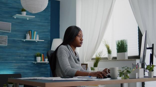 Student mit schwarzer haut, der high-school-universitätsinformationen mit dem computer durchsucht