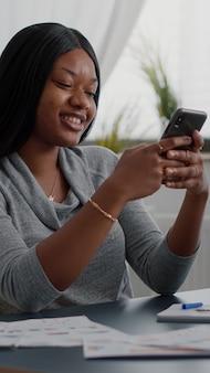 Student mit schwarzer haut-sms-nachricht mit modernem telefon, während er am schreibtisch sitzt und von zu hause aus arbeitet. afroamerikanerin, die auf social media schaut und lifestyle-ratschläge teilt, die mit freunden chatten