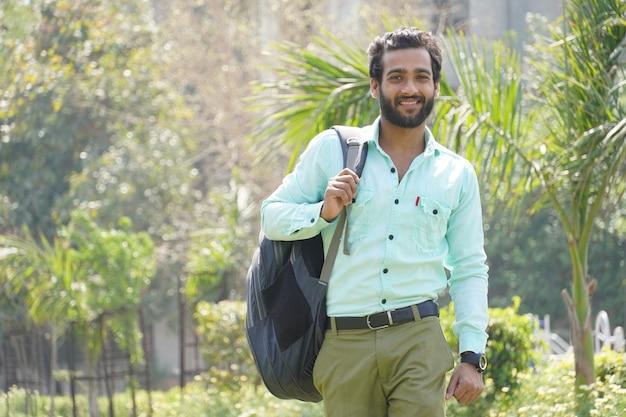 Student mit seiner tasche und büchern auf seinem campus