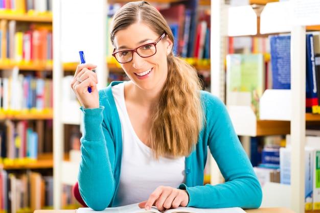 Student mit stapel bücher, die in der bibliothek lernen