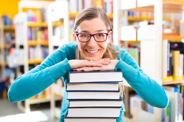 Student mit stapel von büchern lernend in der bibliothek