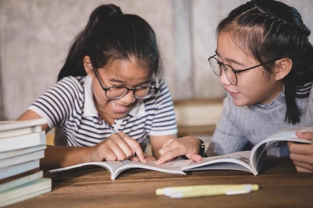 Student mit zwei asiaten, der ein schulbuch mit glückgefühl liest