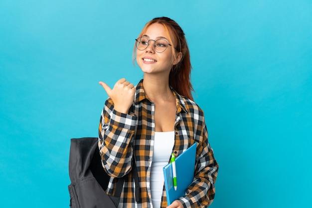 Student russische frau isoliert auf blau zeigt zur seite, um ein produkt zu präsentieren