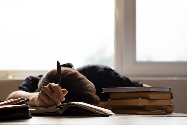 Student schlief für hausaufgaben auf sonnigem hintergrund ein