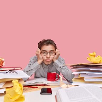 Student sitzt am schreibtisch voller bücher