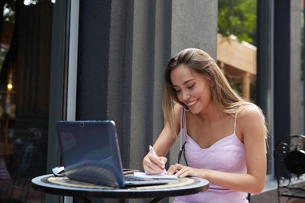 Student sitzt am tisch außerhalb des cafés und lernt mit laptop und macht hausaufgaben