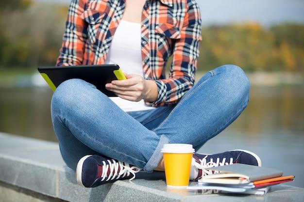 Student sitzt türkisch an der brücke mit tablette