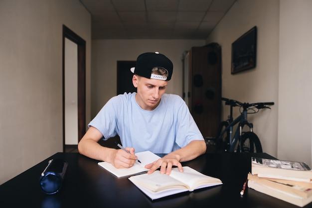Student studiert zu hause. er hält die aufgaben und antworten sorgfältig in seinem notizbuch fest. hausaufgaben