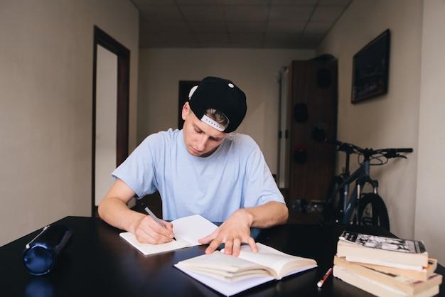 Student studiert zu hause. hausaufgaben. ein teenager mit genauem blick schreibt den text in sein notizbuch