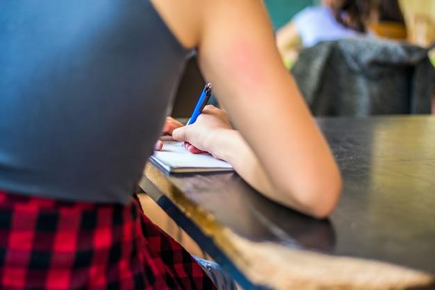 Student studium schriftlich notizen in einem notebook in einem tisch