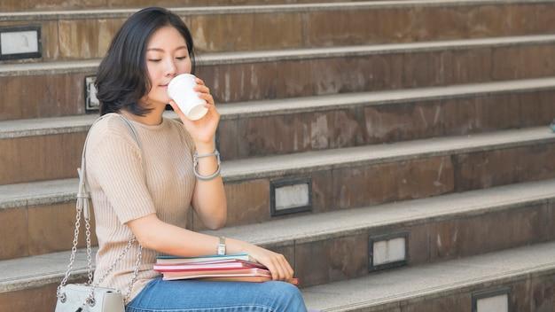 Student teen mädchen mit bildungsbuch und kaffeetasse sitzen auf treppe fußgänger