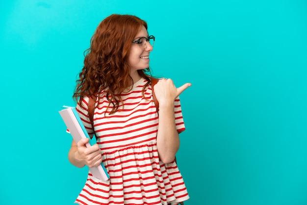Student teenager rothaarige mädchen auf blauem hintergrund isoliert auf die seite zeigend, um ein produkt zu präsentieren
