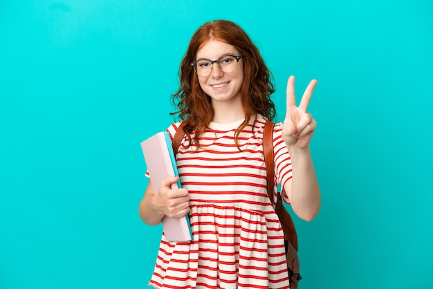 Student teenager rothaarige mädchen isoliert auf blauem hintergrund lächelnd und mit victory-zeichen
