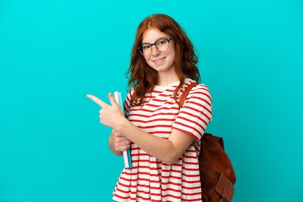 Student teenager rothaarige mädchen isoliert auf blauem hintergrund nach hinten zeigend