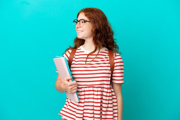 Student teenager rothaarige mädchen isoliert auf blauem hintergrund zur seite schauen und lächeln