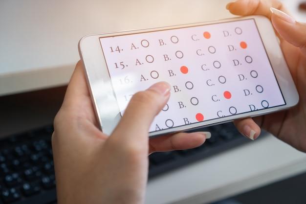 Student testet online-lernen, e-learning-prüfung auf smartphone mit wahlfragen