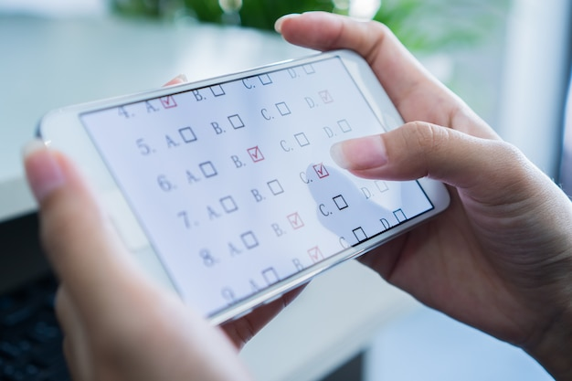 Student testing e-learning-prüfung auf tablet-computer mit multiple-choice-fragen von finge