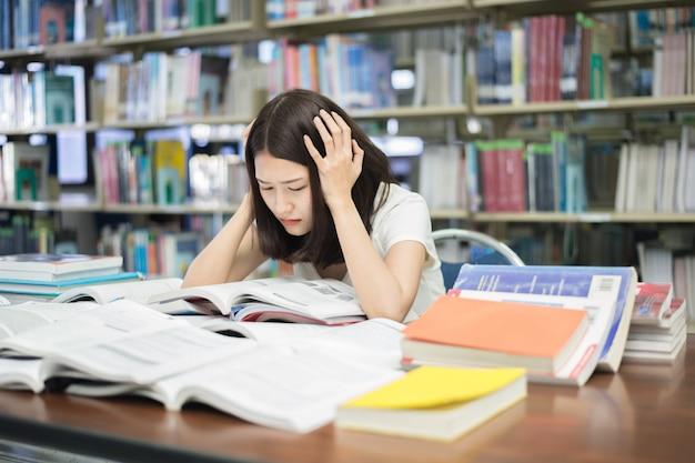 Student unter geistigem druck beim lesen des buches, das prüfung in der bibliothek an der universität vorbereitet.