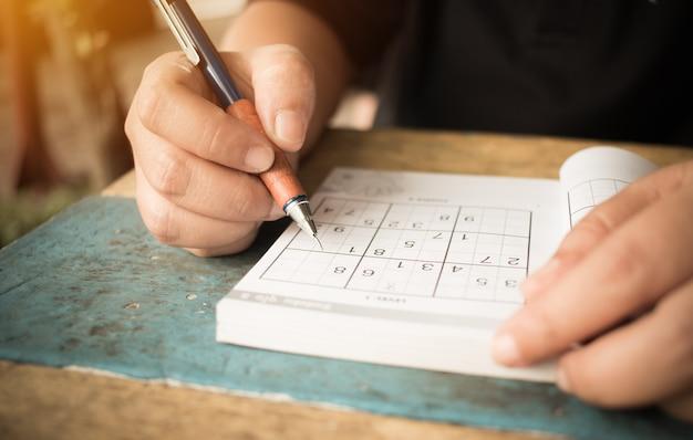 Student versucht sudoku mit farbbleistift als hobby bei im freien zu lösen