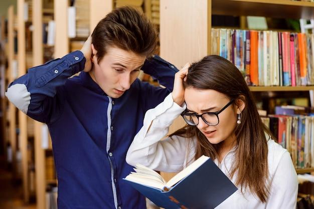 Studenten der bibliothek überprüfen ihre antworten nach der prüfung in einem buch