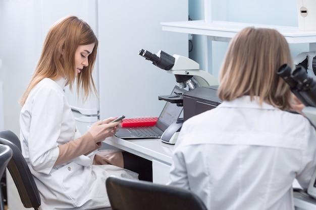 Studenten der fakultät für mikrobiologie oder chemie, die ein mikroskop verwenden