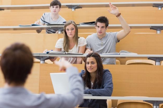 Studenten, die am vorlesungssal mit der razing hand des mannes legen, um frage zu stellen