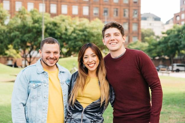 Studenten, die an der kamera auf collegecampus lächeln