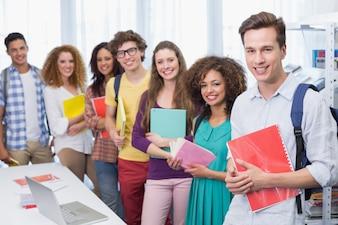 Studenten, die an der Kamera steht in einer Linie am College lächeln