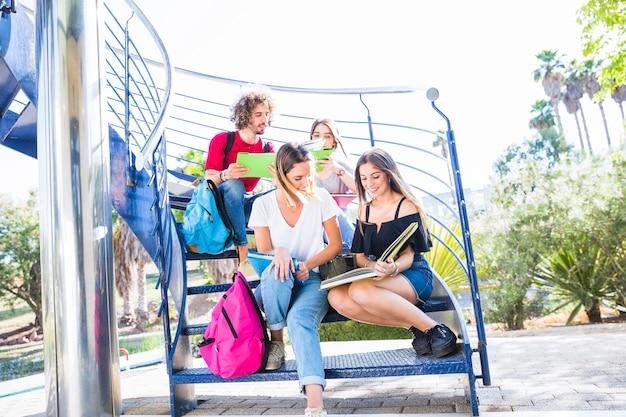 Studenten, die auf blauem treppenhaus studieren