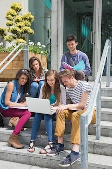 Studenten, die auf den schritten studieren an der universität sitzen