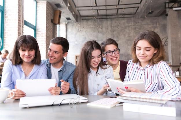 Studenten, die bei tisch sitzen und mit büchern und tablette studieren