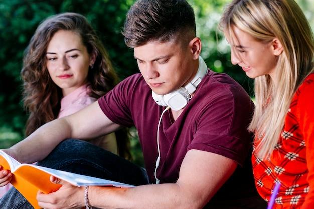 Studenten, die draußen vom notizblock lesen